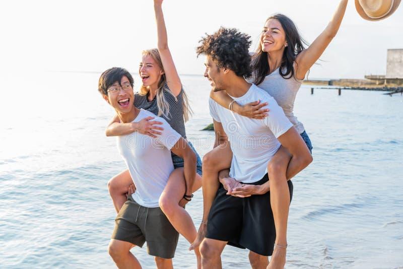 Gruppe Freunde, die entlang den Strand gehen, wenn die Männer piggyback den Freundinnen Fahrt geben Glückliche junge Freunde, die stockbild