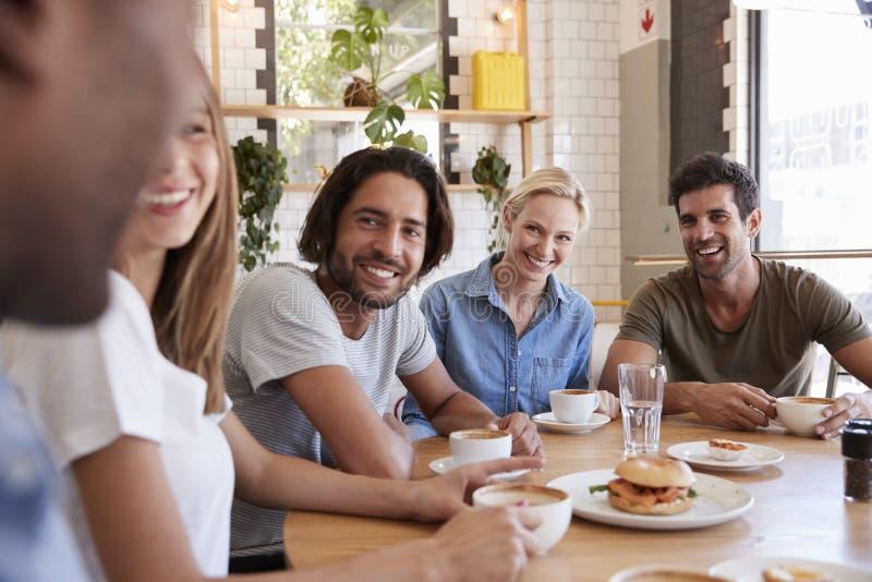 Gruppe Freunde, die für das Mittagessen in der Kaffeestube sich treffen lizenzfreies stockfoto