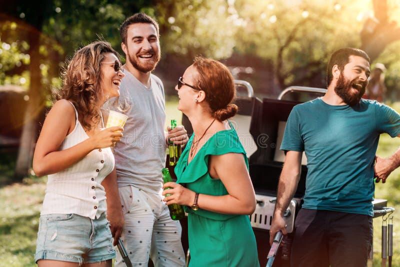 Gruppe Freunde, die Getränke haben und über Grillpartei, Hinterhofkonzept des Sommers im Freien lachen stockbild