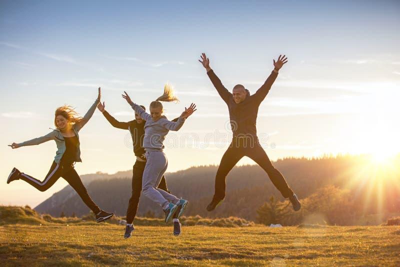 Gruppe Freunde, die glücklich zusammen in das Gras und das Springen laufen stockbilder