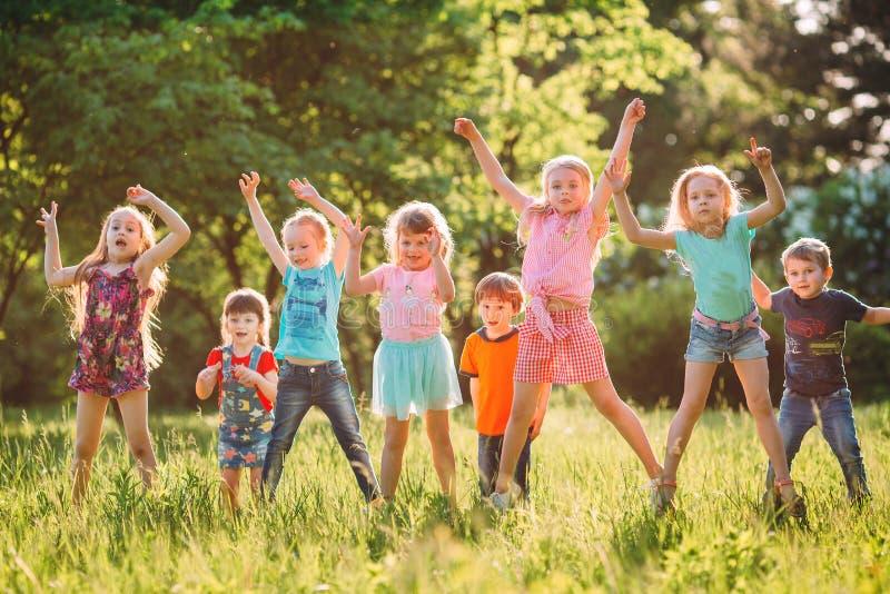 Gruppe Freunde, die gl?cklich zusammen in das Gras und das Springen laufen stockfotografie