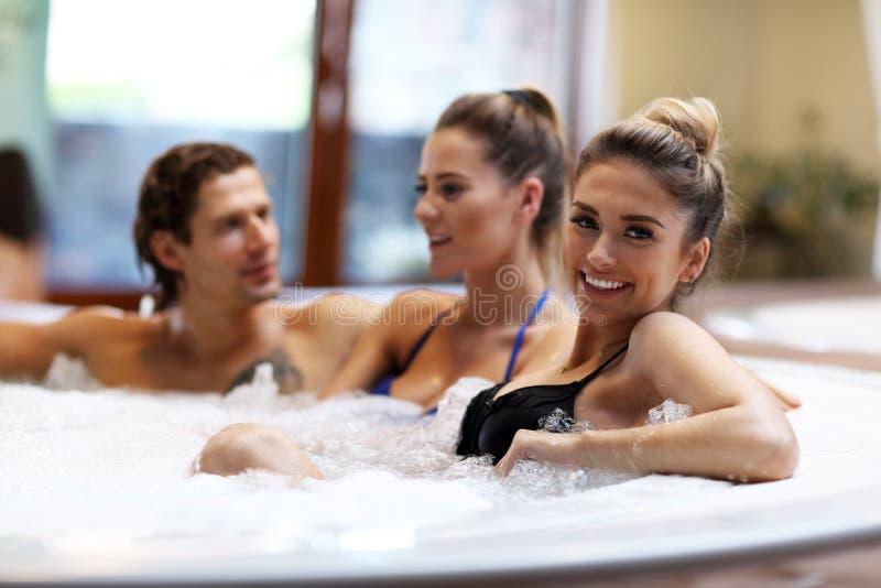 Gruppe Freunde, die Jacuzzi im Hotelbadekurort genießen stockfoto