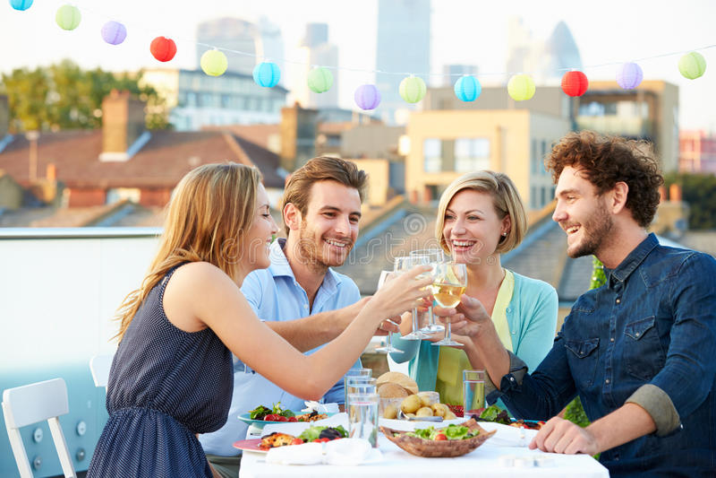 Gruppe Freunde, die Mahlzeit auf Dachspitzen-Terrasse essen stockfoto