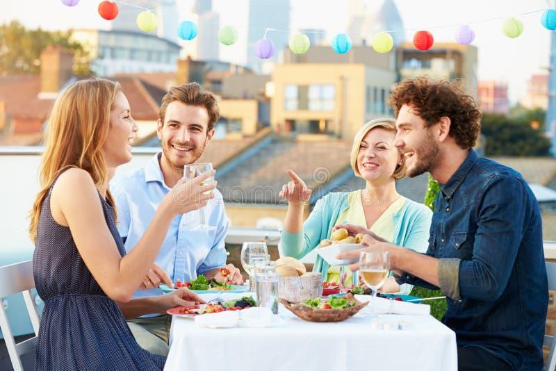 Gruppe Freunde, die Mahlzeit auf Dachspitzen-Terrasse essen stockbilder