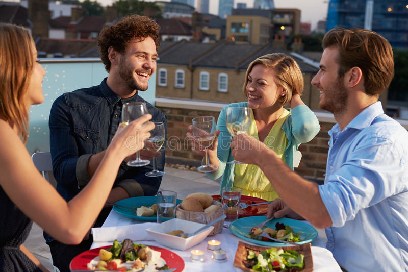 Gruppe Freunde, die Mahlzeit auf Dachspitzen-Terrasse essen stockfotos