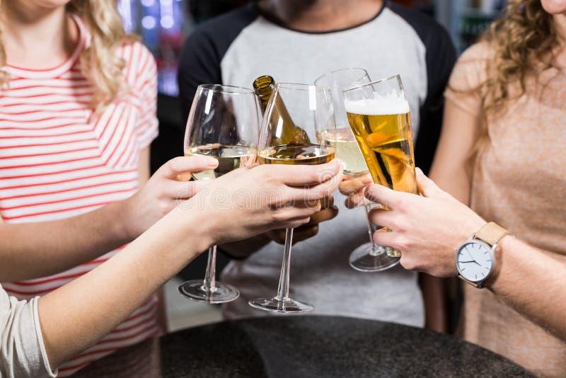 Gruppe Freunde, die mit Bier und Wein rösten lizenzfreie stockfotos