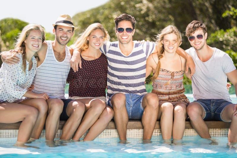 Gruppe Freunde, die nebeneinander am Poolside sitzen lizenzfreies stockbild