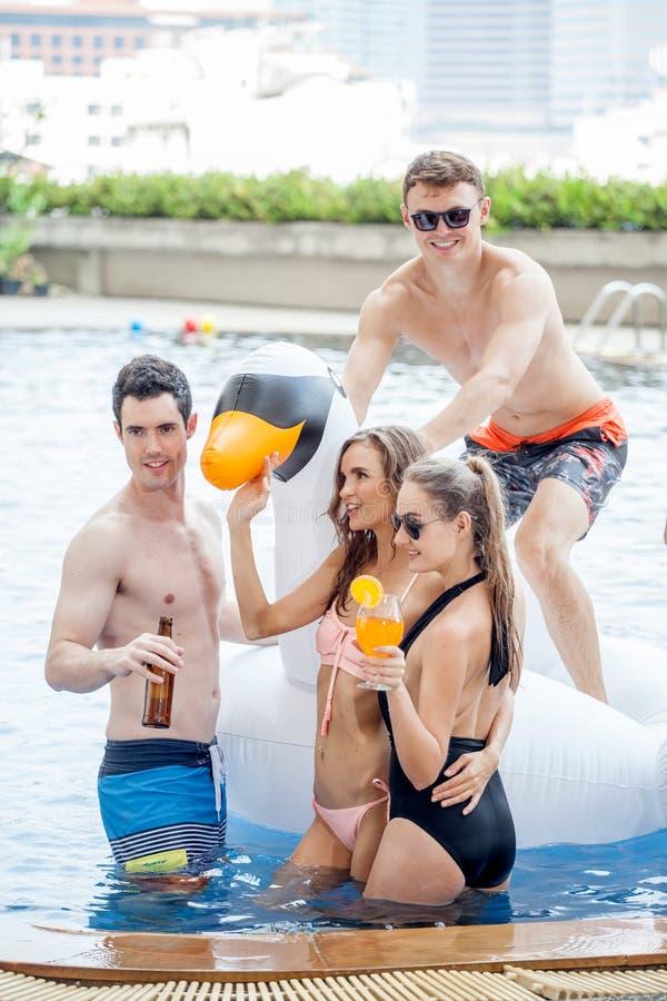 Gruppe Freunde, die Partei im Pool machen und Getränk trinken lizenzfreies stockfoto