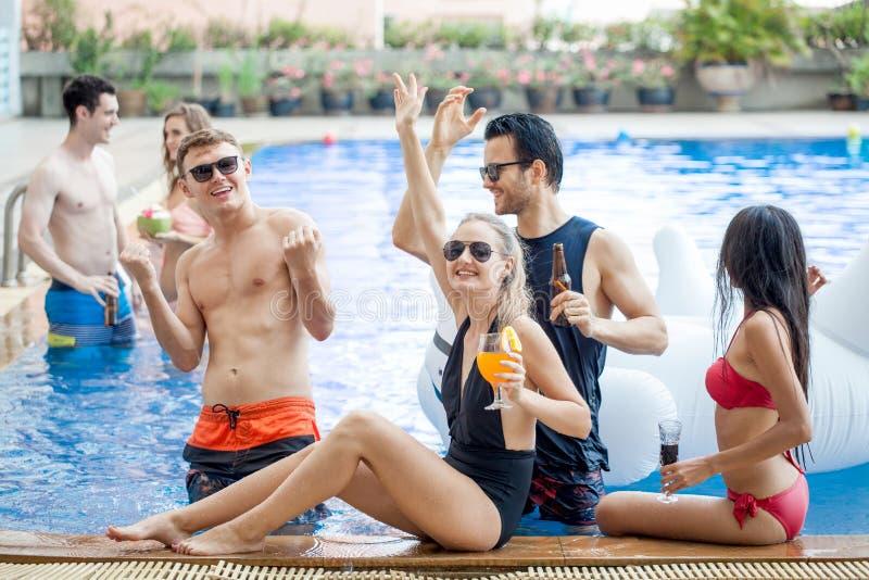 Gruppe Freunde, die Partei im Pool machen und Getränk trinken lizenzfreie stockfotos