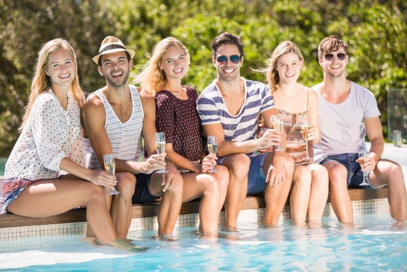 Gruppe Freunde, die am Poolside mit Glas Champagner sitzen stockbilder