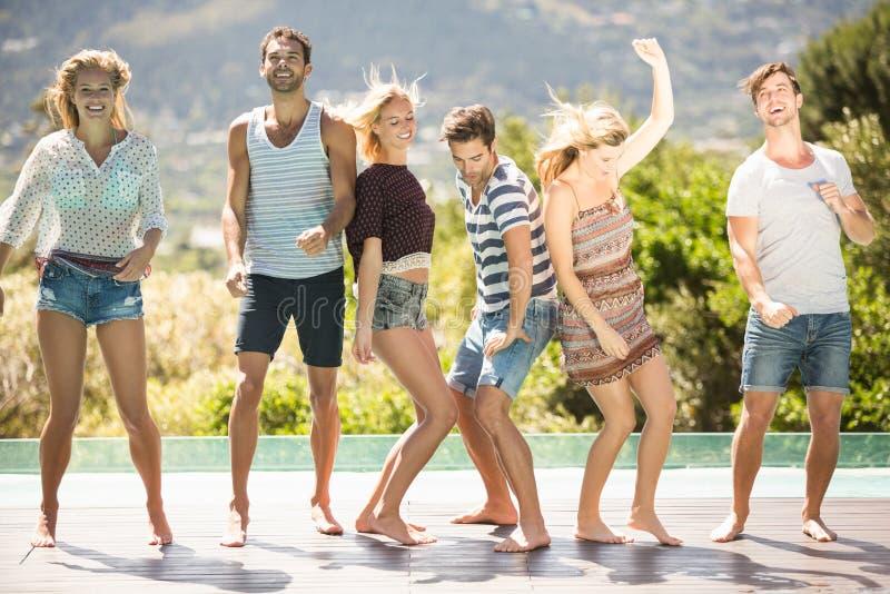 Gruppe Freunde, die am Poolside tanzen lizenzfreie stockbilder