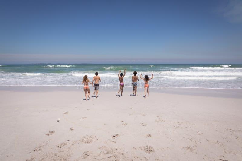 Gruppe Freunde, die in Richtung zum Ozean auf Strand im Sonnenschein laufen lizenzfreies stockbild