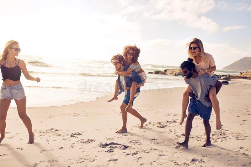 Gruppe Freunde, die Spaß auf dem Strand haben stockbild
