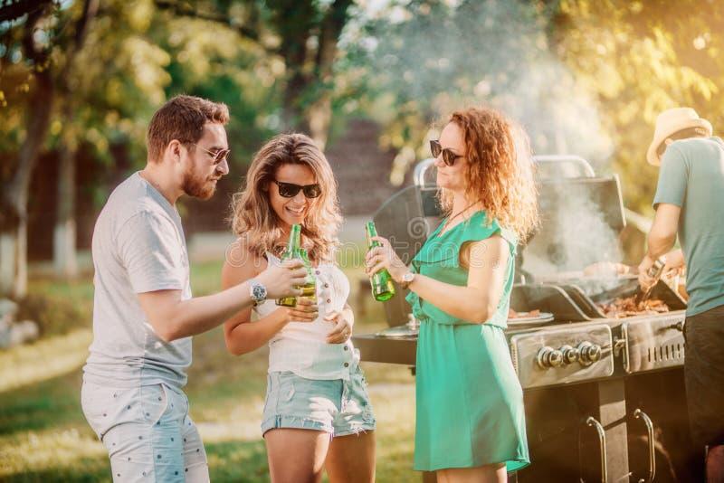 Gruppe Freunde, die Spaß an der Grillpartei, -c$trinken und -c$lächeln und -c$kochen haben lizenzfreie stockfotos