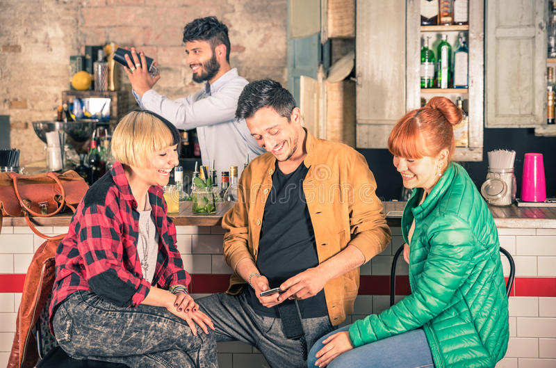 Gruppe Freunde, die Spaß unter Verwendung des Smartphone an der Hippie-Stange haben stockfotografie