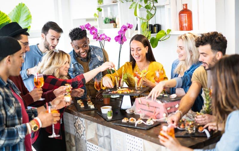 Gruppe Freunde, die Spaß an vor trinkenden Cocktails des Abendessenaperitif-Buffets haben und Imbisse essen lizenzfreie stockfotografie