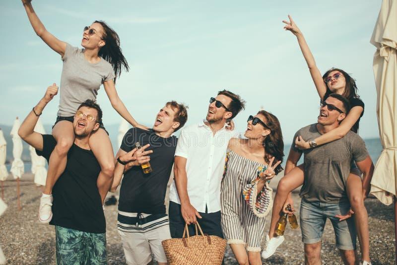 Gruppe Freunde, die am Strand, Spaß, das Doppelpol der Frau habend bemannt gehen an, lustige Ferien stockfotos