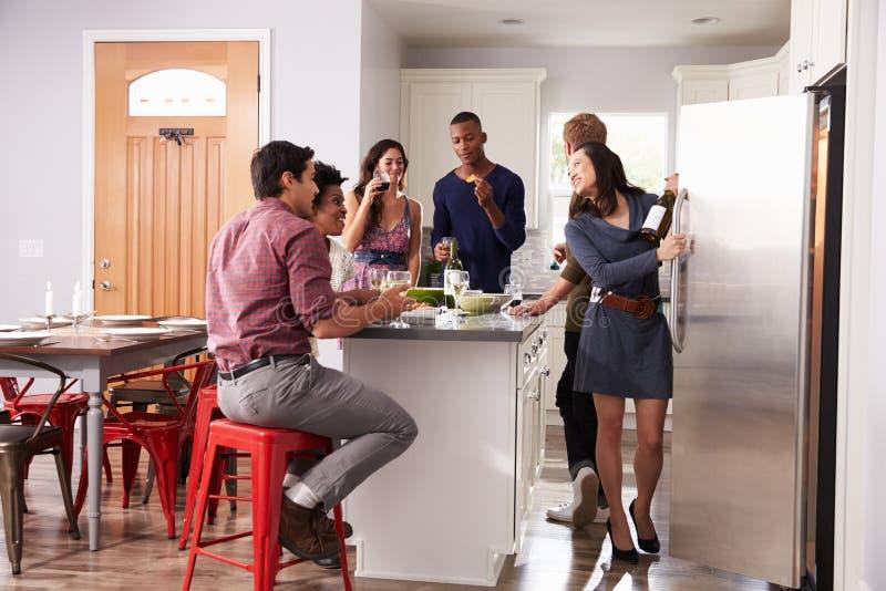 Gruppe Freunde, die vor Abendessen genießen, trinkt zu Hause stockfotografie