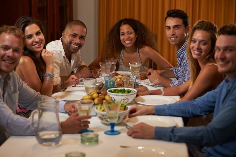 Gruppe Freunde, die zu Hause Abendessen zusammen genießen lizenzfreie stockfotos