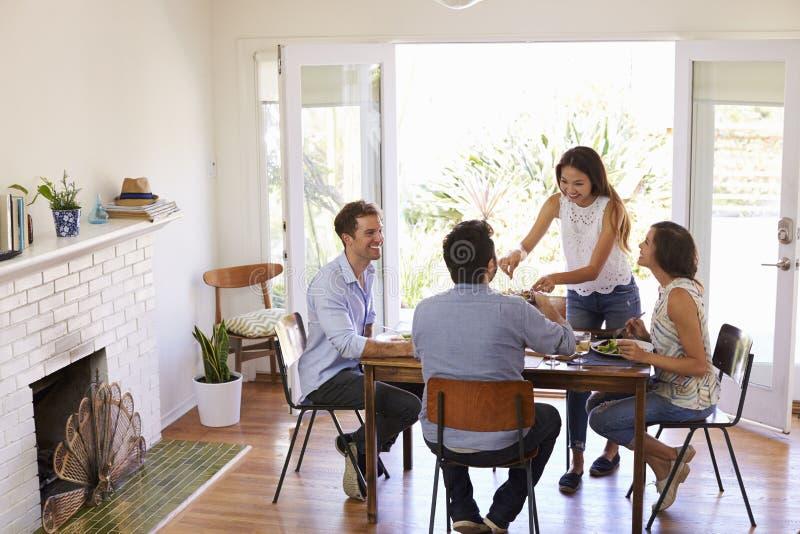 Gruppe Freunde, die zu Hause Abendessen zusammen genießen stockfotos