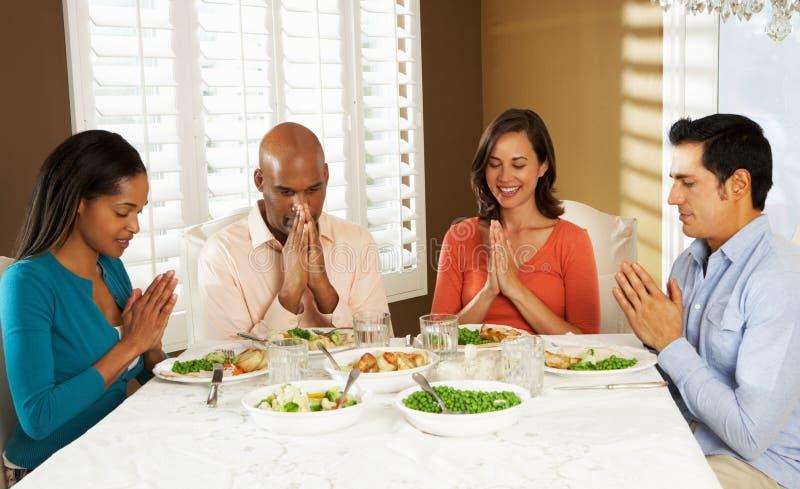 Gruppe Freunde, die zu Hause Anmut vor Mahlzeit sagen lizenzfreie stockfotos