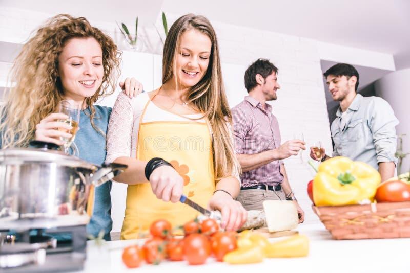 gruppe freunde die zu hause kochen um zu abend zu essen. Black Bedroom Furniture Sets. Home Design Ideas