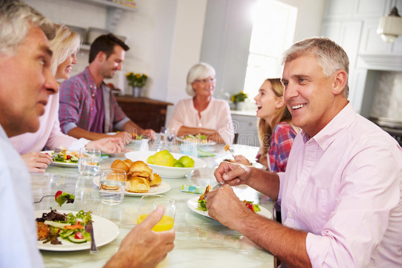 Gruppe Freunde, die zu Hause Mahlzeit zusammen genießen stockbild