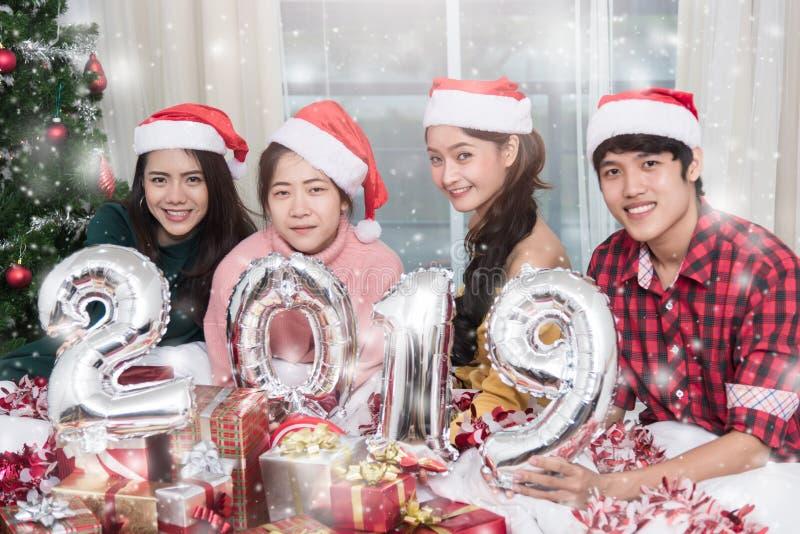Gruppe Freunde, die zu Hause Weihnachten feiern und 2019 zeigen lizenzfreie stockfotos