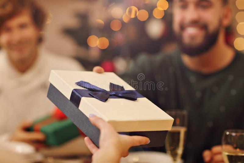 Gruppe Freunde, die zu Hause Weihnachtsgeschenke geben stockfotografie