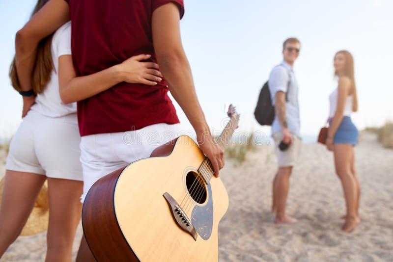 Gruppe Freunde, die zum sandigen Strand bei Sonnenuntergang gehen Junge M?nner und Frauen, die zum Ufer sich nahe Meer und Spiel  stockbilder
