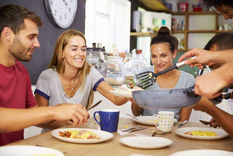 Gruppe Freunde, die zusammen Frühstück in der Küche genießen stockfotos