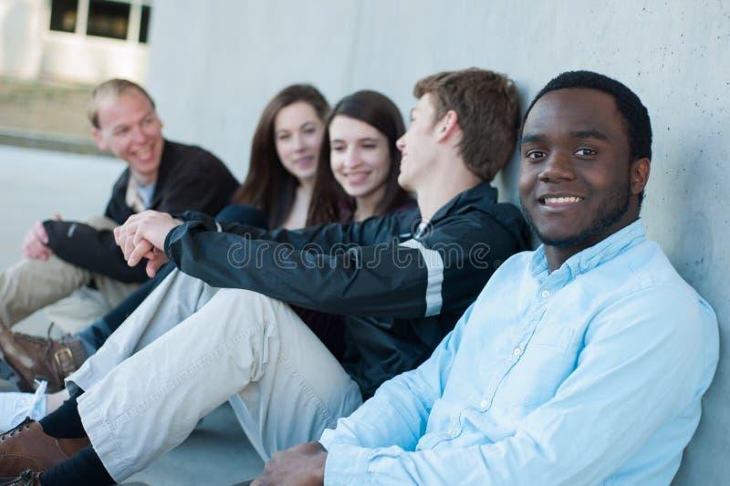 Gruppe Freunde draußen auf dem Campus lizenzfreie stockbilder