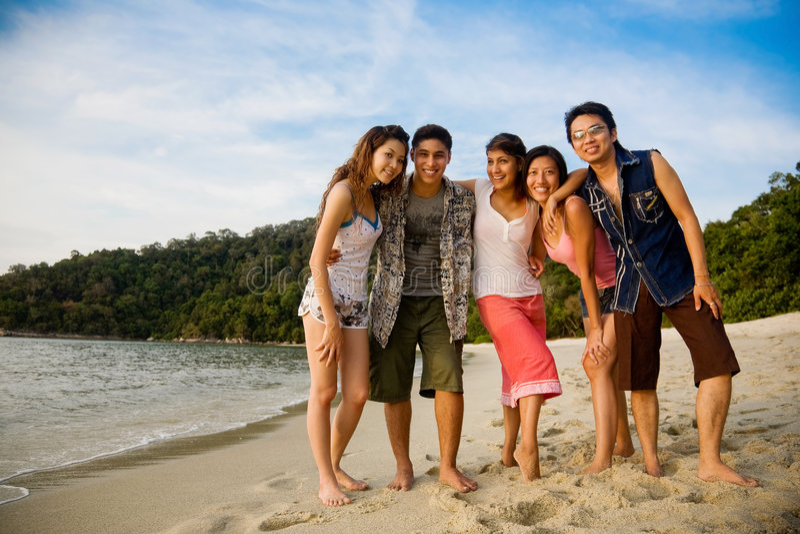 Gruppe Freunde durch den Strand lizenzfreie stockbilder