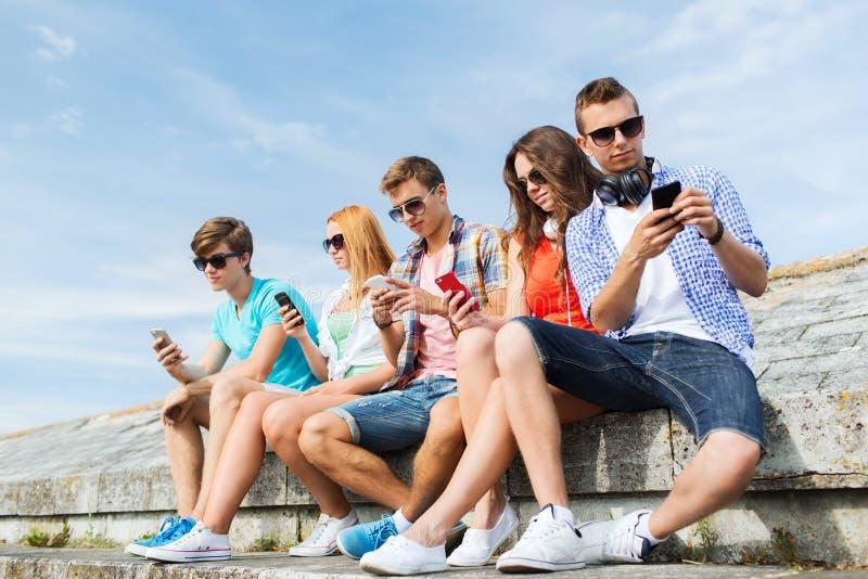 Gruppe Freunde mit Smartphone draußen lizenzfreies stockfoto