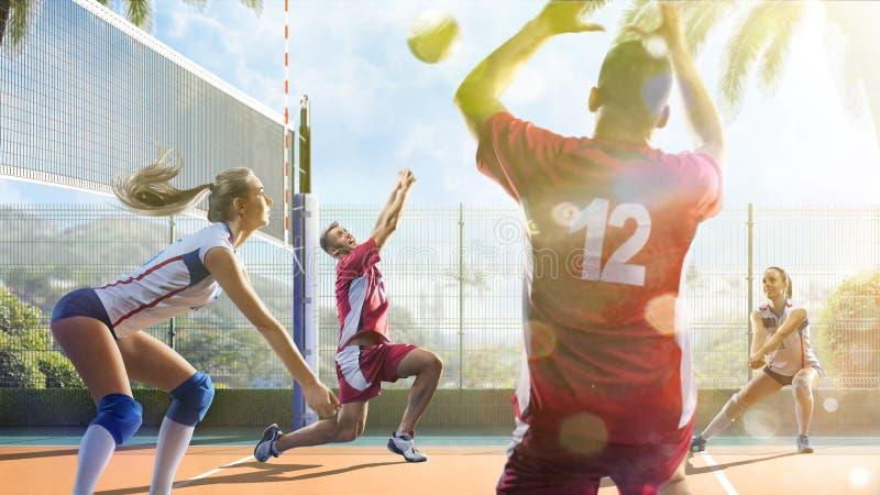 Gruppe Freunde spielt Volleyball am sonnigen Tag stockbilder