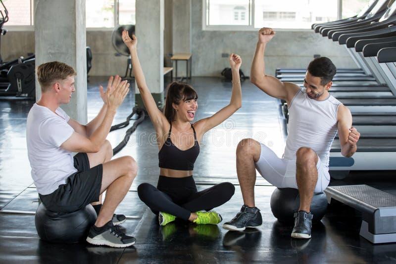 Gruppe Freunde tragen Leute feiern zur Schau und Hände zum Erfolg nach Übung in der Turnhalle anhebend junge Eignung in der Sport lizenzfreies stockfoto