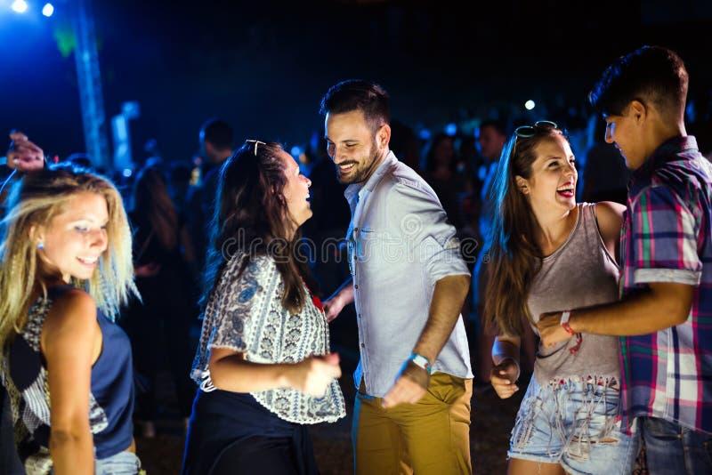Gruppe Freunde, welche die sch?ne Zeit auf Musikfestival haben stockfotos