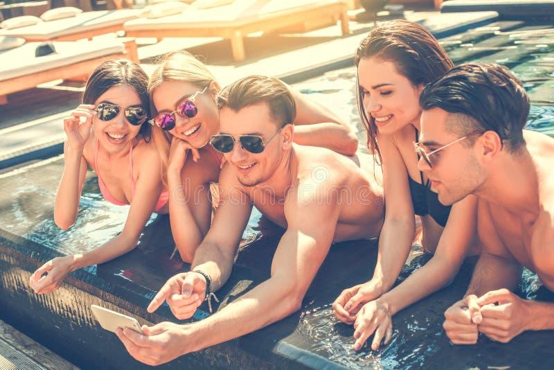 Gruppe Freunde zusammen in der Swimmingpoolfreizeit lizenzfreies stockfoto