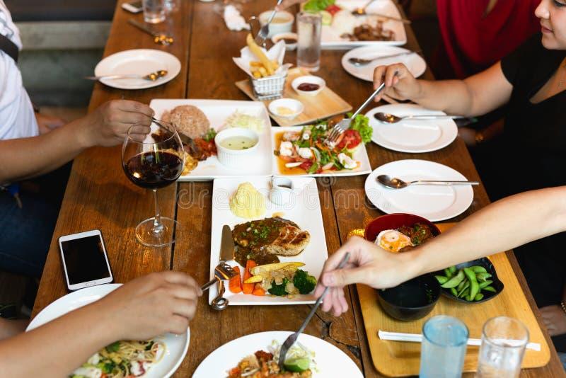 Gruppe Freundhände mit der Gabel, die Spaß Vielzahlnahrung auf dem Tisch essend hat lizenzfreie stockfotos