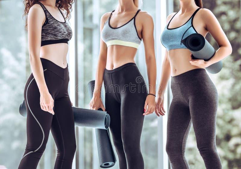 Gruppe Freundinnen in der Sportkleidung zusammen lächelnd bei der Stellung in einer Turnhalle nach Yogatraining stockbild