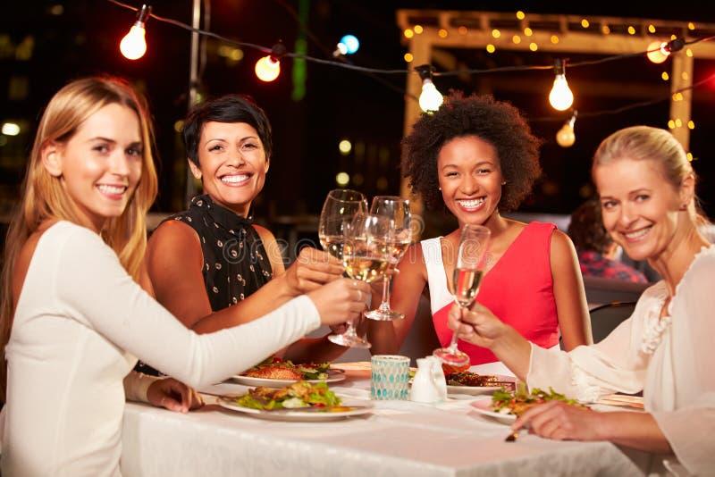 Gruppe Freundinnen, die Abendessen am Dachspitzenrestaurant essen lizenzfreie stockfotografie