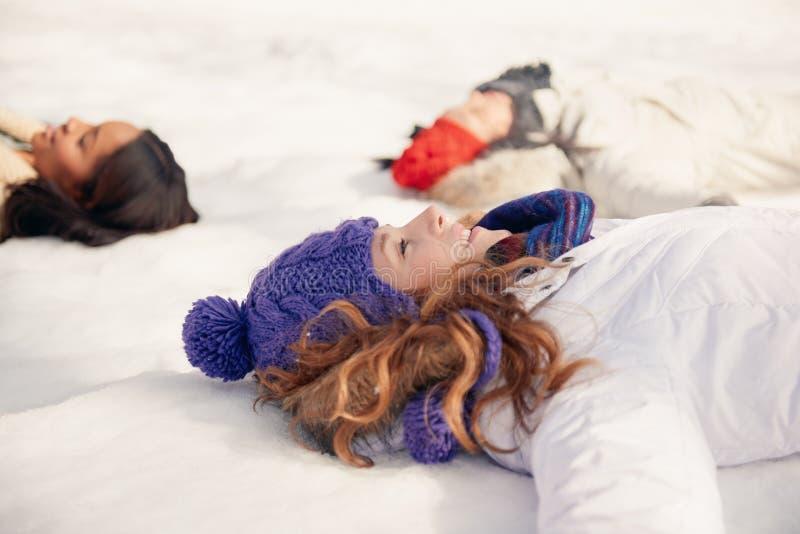 Gruppe Freundinnen, die Schneeengel im Winter machen lizenzfreies stockfoto