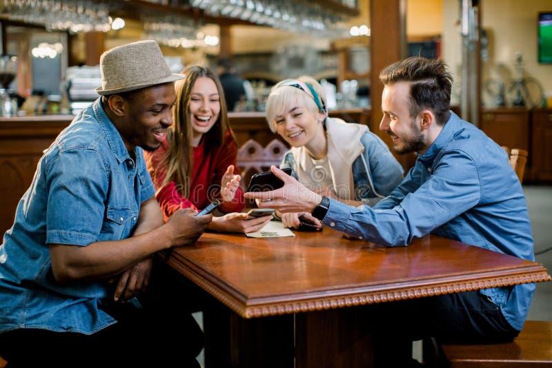 Gruppe gemischtrassige Freunde, die zusammen im Café genießen Junge Leute, die in einem Caf? sich treffen Junge Männer und Frauen lizenzfreies stockfoto