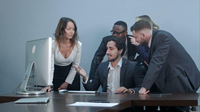 Gruppe gemischtrassige Geschäftsleute um den Konferenztisch, der Laptop-Computer betrachtet und mit gegenseitig spricht lizenzfreie stockfotografie