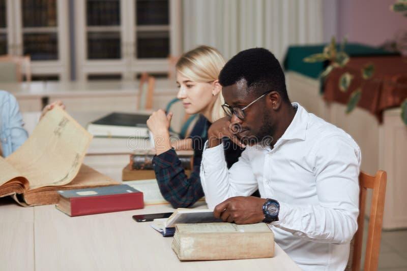 Gruppe gemischtrassige Leute, die mit Büchern in der Collegebibliothek studieren stockbilder