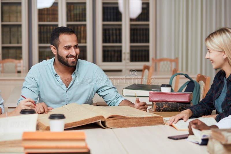 Gruppe gemischtrassige Leute, die mit Büchern in der Collegebibliothek studieren stockfotografie