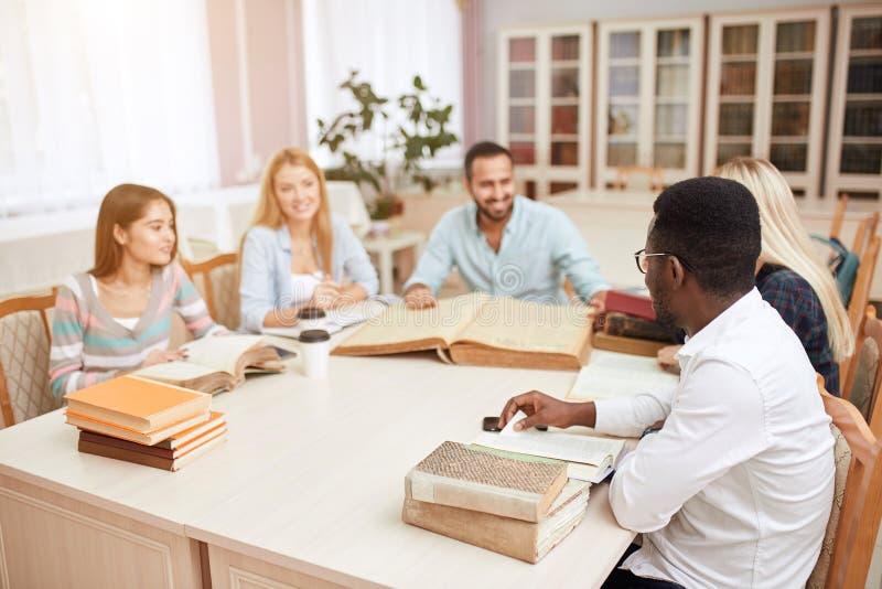 Gruppe gemischtrassige Leute, die mit Büchern in der Collegebibliothek studieren stockbild