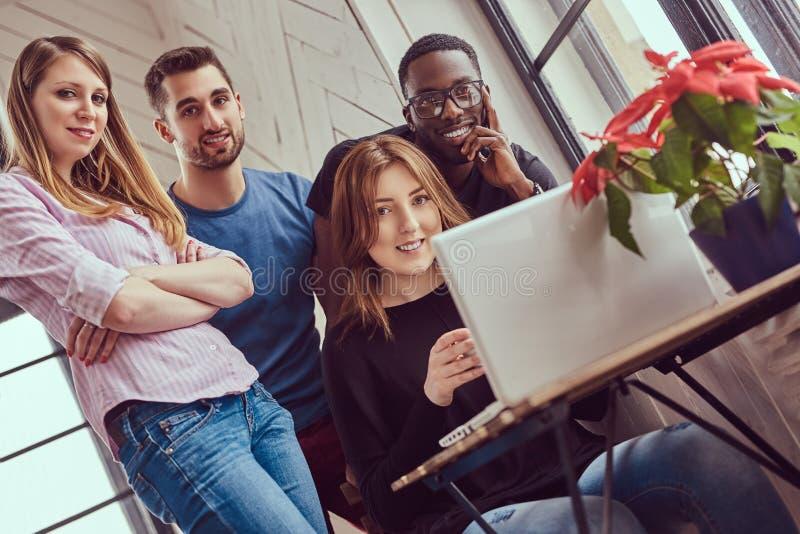 Gruppe gemischtrassige Studenten, die mit einem Laptop arbeiten lizenzfreies stockbild