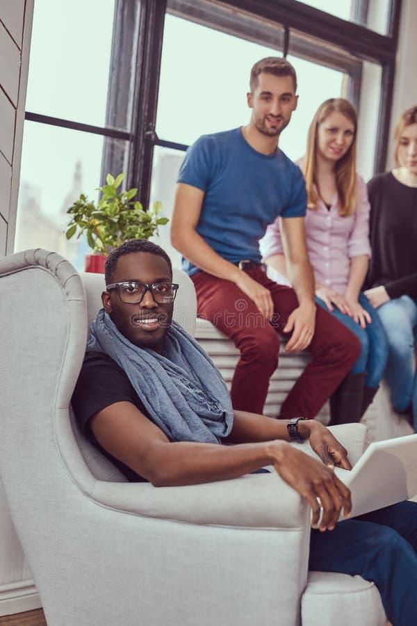 Gruppe gemischtrassige Studenten, die mit einem Laptop arbeiten stockfotografie