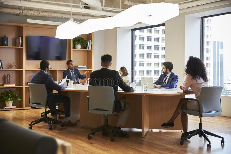 Gruppe Geschäfts-Fachleute, die um Tabelle im modernen Büro sich treffen stockfotografie